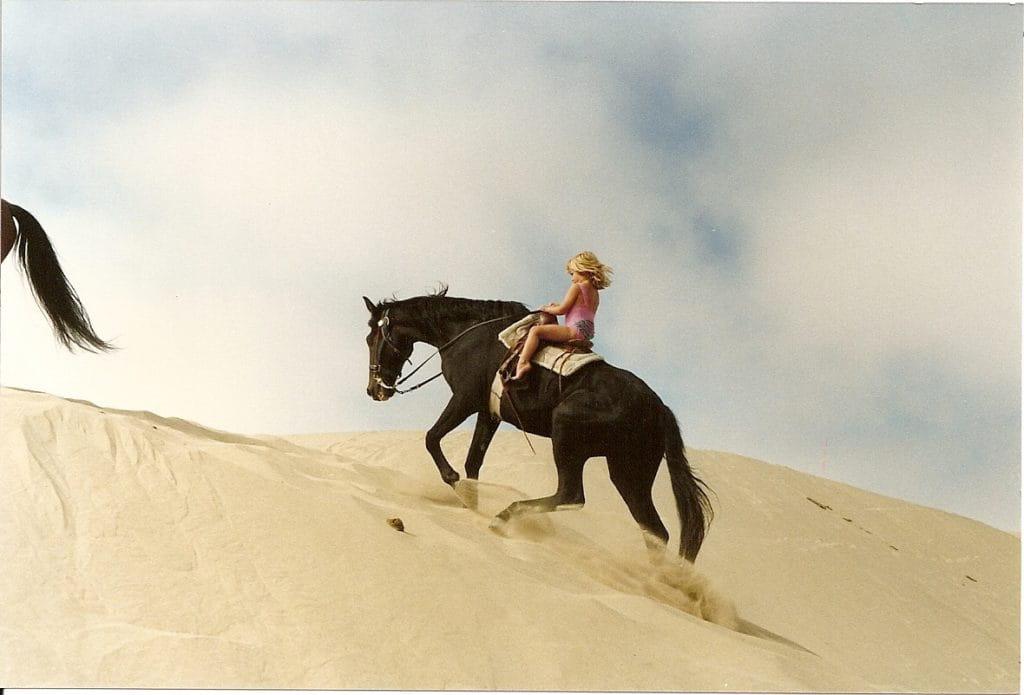 Alison Tetrick Oso Flaco Dunes. Girl on horse riding up sand dunes.