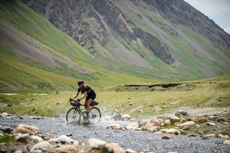Alison Tetrick crossing stream on gravel bike in Kyrgyzstan