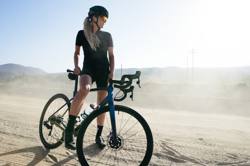 Alison Tetrick on a gravel road with her gravel bike