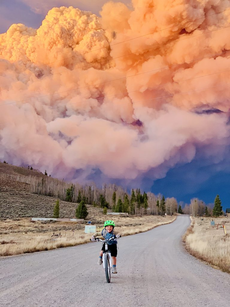 A boy on his mountain bike in Granby Colorado during the Troublesome Fire on October 21, 2020.