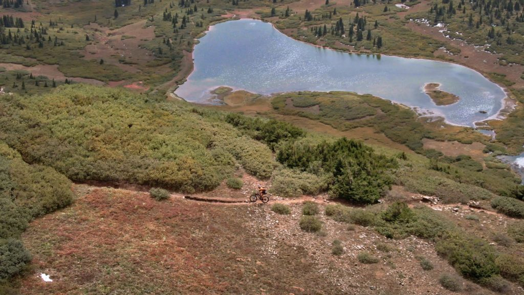 Payson McElveen mountain biking above a lake somewhere along his Colorado Trail FKT attempt