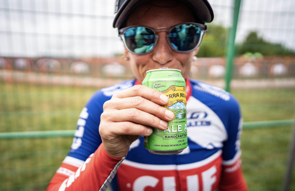 Cyclist Katerina Nash drinking a beer after a race